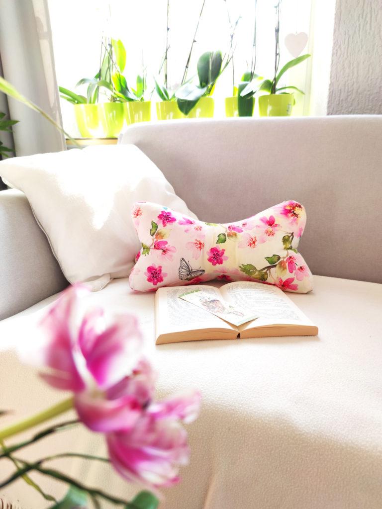 Leseknochen mit pinken Blüten auf Sofa
