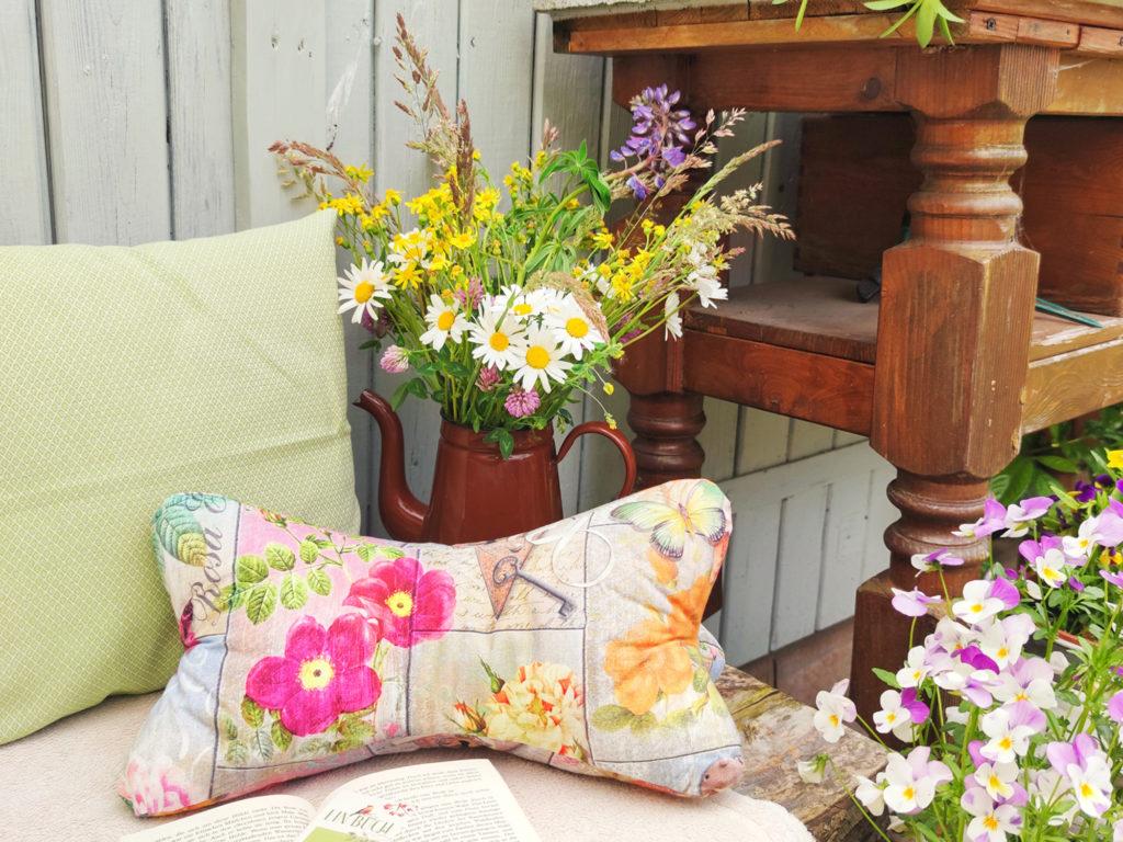Blumen-Leseknochen-Kissen-hellgrün-Rauten-auf-der-Bank